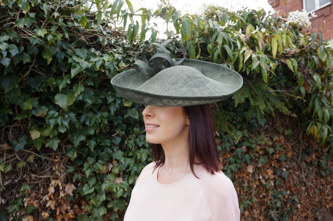 An olive green sinamay headpiece, trimmed with sinamay.